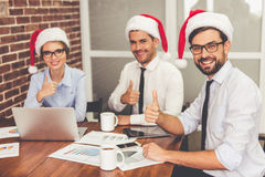 Business people celebrating Christmas. Happy business people in Santa hats are showing Ok sign and smiling while celebrating New Year in office Stock Photography