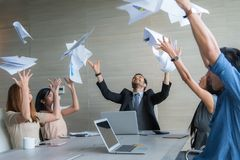 Business people celebrating by throwing documents after working stock photography