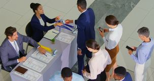 Business people checking in at conference registration table 4k. High angle view of business people standing in line before checking in at the conference stock footage