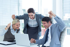 Business people cheering in front of laptop at office Stock Photos