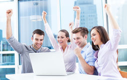Business people cheering at laptop Royalty Free Stock Photos