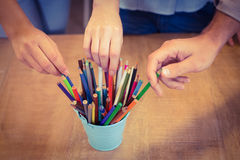Business people choosing pencils from desk organizer Stock Photos