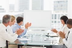 Business people clapping at blank whiteboard in conference room Stock Photos