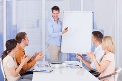 Business people clapping for colleague after presentation. Young business people clapping for male colleague after presentation in office Stock Photo