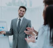 Successful business man in suit at the office leading a group. Business people clapping at conference. Business presentation Royalty Free Stock Image