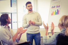 Business people clapping for confident male colleague Royalty Free Stock Photography