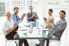 Business people clapping hands in board room meeting. Young business people clapping hands in board room meeting at office Stock Images