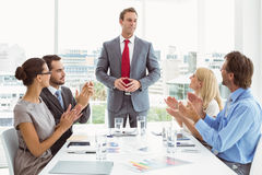 Business people clapping hands in board room meeting. Young business people clapping hands in board room meeting at office Royalty Free Stock Image