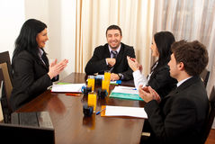 Business people clapping hands  at meeting. Three business people applauding and congratulate their colleague man Stock Photo