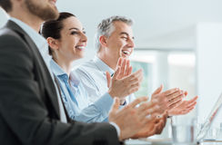 Business people clapping hands during a seminar. Cheerful smiling business people clapping hands during a seminar, success and achievement concept royalty free stock photo