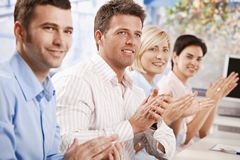 Business people clapping at meeting. Happy business people sitting at table in meeting room clapping listening to presentation Royalty Free Stock Photography