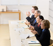 Business people clapping in meeting. Business people clapping and smiling in a meeting Royalty Free Stock Image
