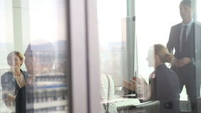 Business people clapping to colleague in conference room, behind glass wall stock video