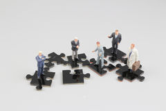 Business people collaborate holding up jigsaw puzzle pieces Stock Image
