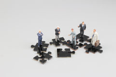 Business people collaborate holding up jigsaw puzzle pieces Stock Photography