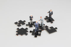 Business people collaborate holding up jigsaw puzzle pieces Royalty Free Stock Images