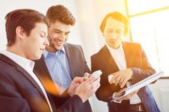 Business people communicating as team. With smartphone in start-up Stock Image
