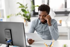 Businessman calling on smartphone at office. Business, people, communication and technology concept - smiling african american businessman with papers and Stock Photos