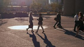 Business people commuting on a busy city street. Early in the morning. Commuters walking on a city street going to office. Zoom out shot stock footage