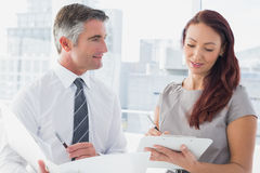 Business people comparing work notes Stock Image
