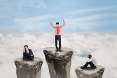 Business people competition above cloud outdoor. Business people on top of rocks with one winner exulting above clouds Royalty Free Stock Image