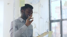 Businessman with clipboard at office glass wall. Business and people concept - african american businessman with clipboard looking at charts on office glass stock video footage