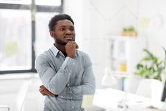 Businessman looking at glass board at office. Business and people concept - african american businessman looking at chart on glass board at office Stock Photography