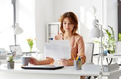 Businesswoman with papers drinks coffee at office. Business and people concept - businesswoman with papers at working office and drinking coffee Stock Photos