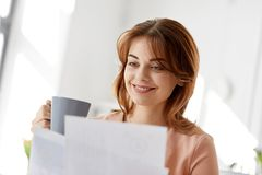 Businesswoman with papers drinks coffee at office. Business and people concept - businesswoman with papers at working office and drinking coffee Stock Images