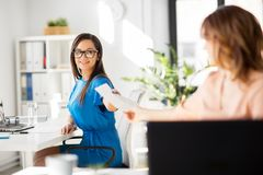 Businesswomen giving each other papers at office. Business and people concept - businesswomen giving each other papers at office Royalty Free Stock Photo
