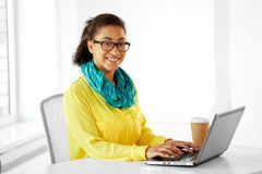 Creative woman with laptop and coffee at office royalty free stock images