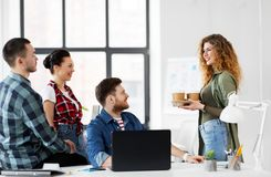 Happy creative team with coffee working at office royalty free stock image