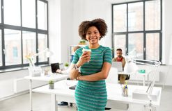 Smiling african woman drinking coffee at office. Business and people concept - happy smiling african american women with smart watch drinking coffee at office stock image