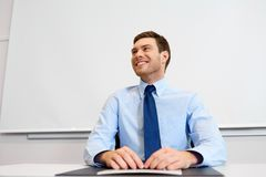 Smiling young businessman sitting at office table Royalty Free Stock Photography