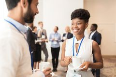 Business people with conference badges and coffee Royalty Free Stock Images