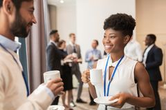 Business people with conference badges and coffee. Business, communication and education concept - international group of people with conference badges drinking royalty free stock photo