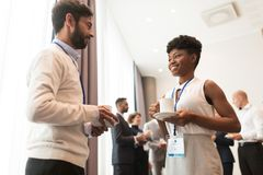 Business people with conference badges and coffee. Business, communication and education concept - international group of people with conference badges drinking royalty free stock images