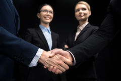 Business people connecting and shaking hands while businesswomen looking on them isolated on black. Business handshake concept royalty free stock photos