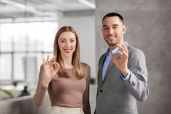 Businesswoman and businessman showing ok at office Stock Photo