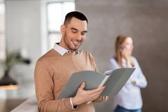 Smiling male office worker with folder Stock Image