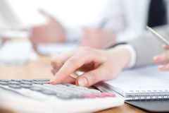Business people counting on calculating machine Stock Images