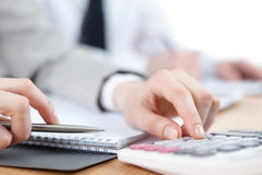 Business people counting on calculator Stock Image