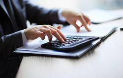 Business people counting on calculator sitting at the table. Royalty Free Stock Photography
