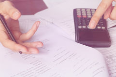 Business people counting on calculator sitting at the table. Close up of hands and stationery Royalty Free Stock Photography