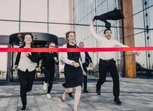 Business people crossing the finish line. Group of happy business people running from office building crossing red ribbon finish line Royalty Free Stock Images