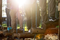 Business People Crossing Swinging Logs In Forest. Low section of business people crossing swinging logs in forest on sunny day stock photography