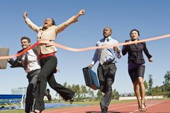 Business People Crossing The Winning Line. Low angle view of business people crossing the finish line royalty free stock images