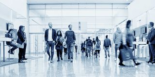 Business people crowd at an trade show concept. Crowd of business people walking in a modern hall at a trade show. ideal for websites and magazines layouts stock image