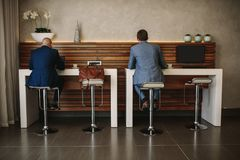 Business people at cyber corner in international airport. Rear view shot of two businessmen sitting at free internet service counter in airport lounge. Business Royalty Free Stock Photography