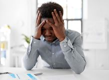 Stressed businessman with papers at office. Business, people and deadline concept - stressed african american businessman with papers at office Royalty Free Stock Image